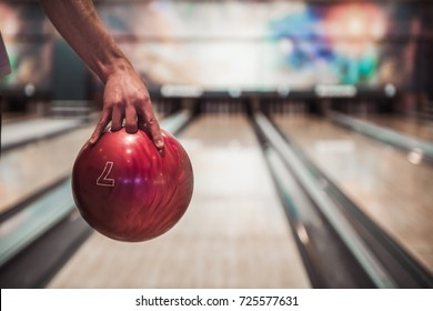 Man's hand holding a red bowling ball ready to throw it
