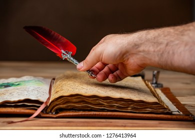 A mans hand holding a red and silver quill pen and writing in an old book resting on a wooden table.