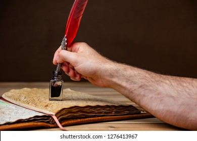 A mans hand holding a red and silver quill pen and dipping ink on an old book resting on a wooden table.