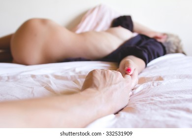 Man's hand holding sexy nude blonde woman sleeping in the bed in brown man's shirt