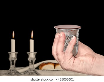 Man's hand holding silver kiddush cup for the Jewish sabbath. Filled to the brim with red wine. Shabbat candles and challah bread in blurred black background.