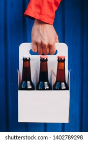 Man's Hand holding a six pack of brown beer bottles