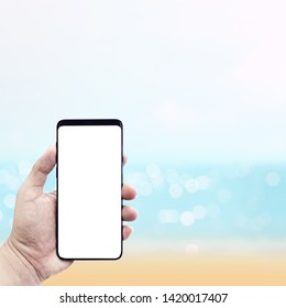 Man's hand holding smartphone with blur sea in sammer background.