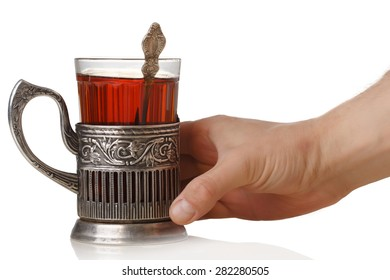 Man's hand holding a soviet faceted glass of tea (stakan) with teaspoon standing into vintage glass-holder (podstakannik)