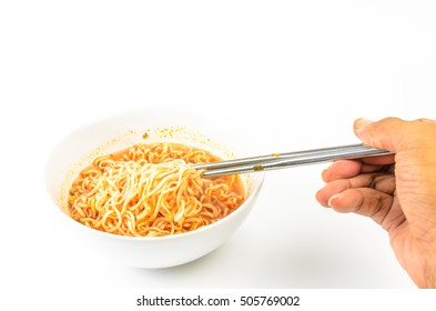 Man's hand holding stainless steel chopsticks of instant noodles