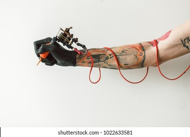 Man's hand holding tattoo machine on white background. the red wires