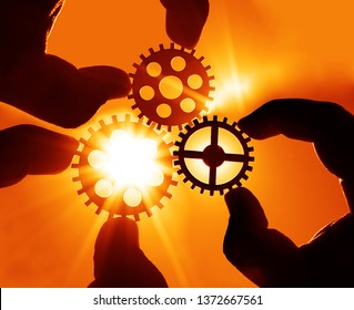Man's hand holding three 3 wooden cog gear wheel on blue sky background. sunshine and yellow sky . sun rays. business team concept.