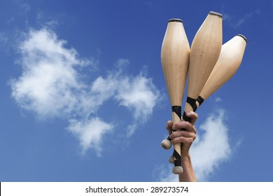 man's hand holding three wooden juggling clubs in the blue sky, metaphor for talent, assiduity, skill and success, copy space