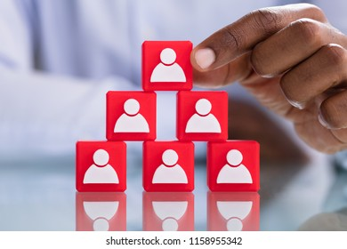 Man's Hand Holding A Top Of Blocks Pyramid With People Icons Over Red Blocks