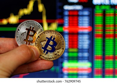 Man's hand holding two bitcoins on stock's chart background