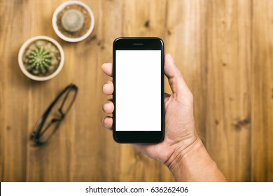Man's hand holding using black smartphone isolated white screen on wooden background with eyeglasses and cactus flower, mobile phone blank screen for mock up design