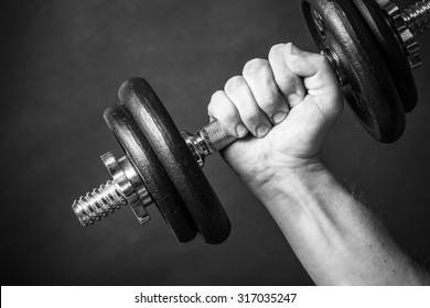 Man`s hand holding weight. Body building in studio, black and white.