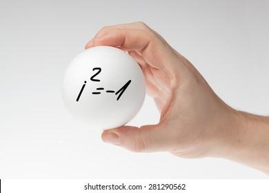 Man's hand holding white blank styrofoam ball with handwritten imaginary number formula against the white background.