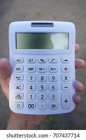 A man's hand holding a white calculator with soil background.