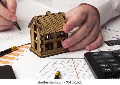 man's hand holding a wooden house on the table