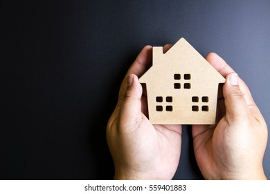 Man's hand holding wooden house toy on black background with copy space.Real estate concept, New house concept, Finance loan business concept