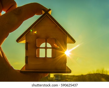 Man's hand holding a wooden toy house with window against blue sky. sun rays. sun light. eco bio building