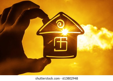 Man's hand holding a wooden toy house with window against blue sky. sun rays. sun light. eco bio building sweet home. house for rent