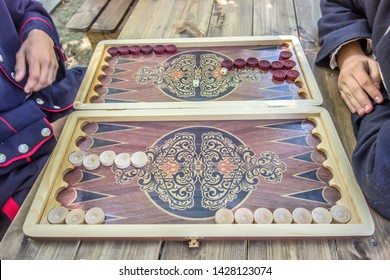 Man's hand holds a backgammon game. Backgammon playing field and dices - games vintage background