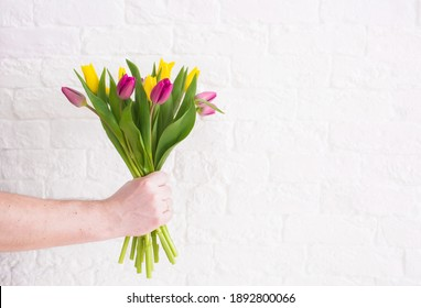 "A man's hand holds a beautiful bouquet of tulips against a white brick wall. The concept of the celebration. Greeting card for women's Day on March 8. March 8 and the concept of ""women's day""."