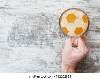 man's hand holds a beer mug with a football on a beer foam. Top view. Space for text
