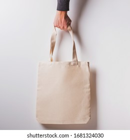 Man's hand holds blank cotton eco tote bag over the white wall, design mockup.