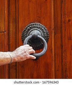 Man's hand holds the cast iron door knocker on the old door in Italy
