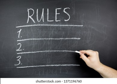 A man's hand holds chalk. A list of rules is written on a chalkboard