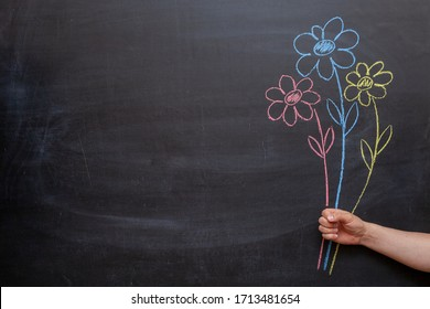 A man's hand holds flowers drawn on a chalkboard in his hand.