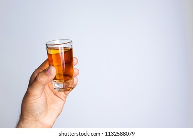 A man's hand holds a glass with liquid on a gray background