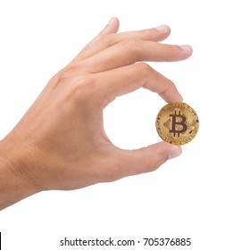 Man's hand holds a gold coin bitcoin coin. The symbol is OK. Isolated on white