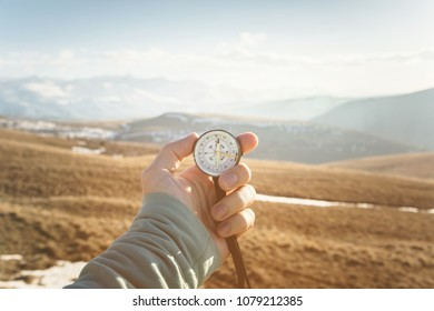 a man's hand holds a hand-held compass against the backdrop of mountains and hills at sunset. The concept of travel and navigation in open areas
