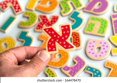 Mans hand holds the Hebrew letter Alef ( Aleph)over Hebrew alphabet letters and characters background.
