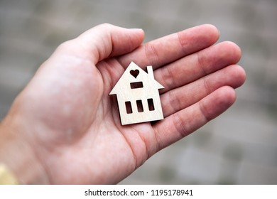 A man's hand holds the house figure