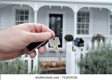 A man's hand holds a key against a front of a traditional villa house in Auckland, New Zealand. Buy, sale, real estate, insurance, mortgage, bank loans and housing market concept.