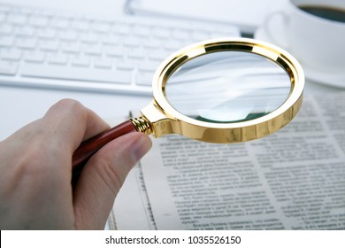man's hand holds a magnifying glass over a newspaper font