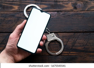 Man's hand holds a modern smartphone with a white screen, handcuffs lie against a wooden background