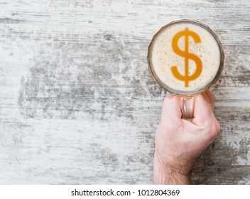 man's hand holds a mug of beer with sign of a  dollar usa  on a beer foam. Top view. Space for text