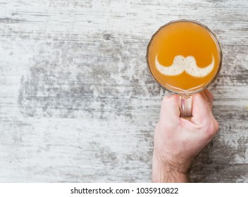 man's hand holds a mug of beer with silhouettes of mustache on a beer foam. Top view. Space for text