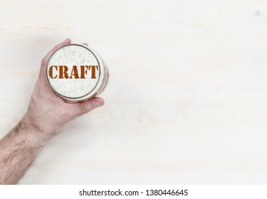 """man's hand holds a mug of beer with silhouettes of word """"craft"""". Top view. Empty space for text"""