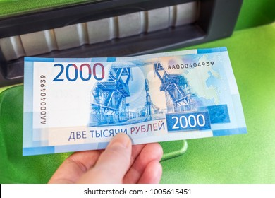 Man's hand holds a new Russian banknote of two thousand rubles against the background of green cash machine