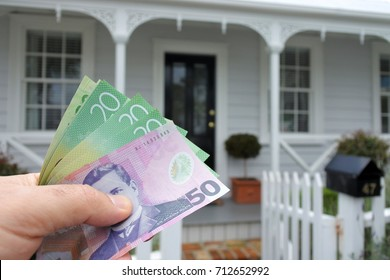 A man's hand holds NZ dollar bills against a front of a traditional villa house in Auckland, New Zealand. Buy, sale, real estate, insurance, mortgage, bank loans and housing market concept.