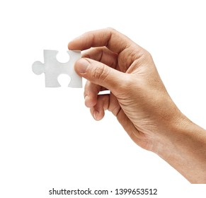 Man's hand holds one puzzle element isolated on white background. Close up. High resolution product