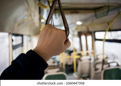 The man's hand holds onto the red handle of the handrail in public transport