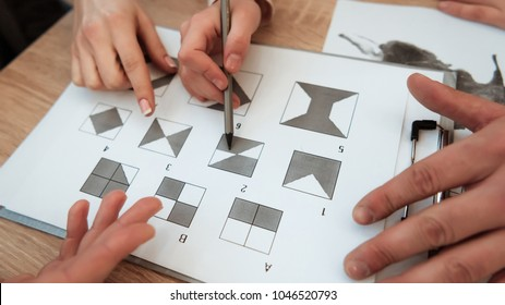 Man's hand holds pencil to make a mark on graphic test. Man is passing psychological graphic test. Passing of psychological test with figures on sheet of paper.