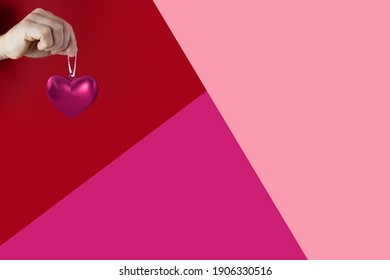 man's hand holds pink heart, geometric red, pink background, symbol of love, concept of confession, Valentine's Day, declaration of love, marriage proposal