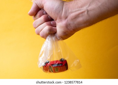 a man's hand holds a plastic transparent bag in which a toy red car, yellow background