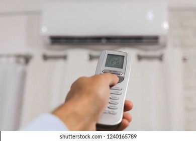man's hand holds a remote control directed on the air conditioner