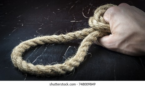 A man's hand holds a rope with a loop, the concept of self-sacrifice