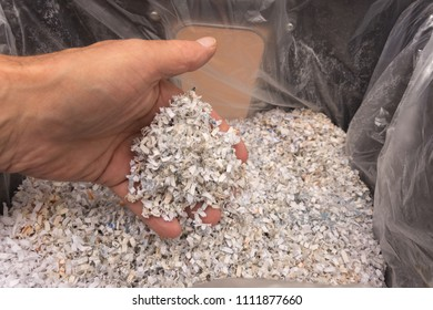 Man's hand holds scraps of paper in his fingers